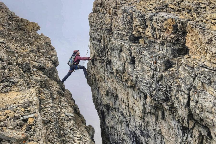 Climber makes wide step over crevasse