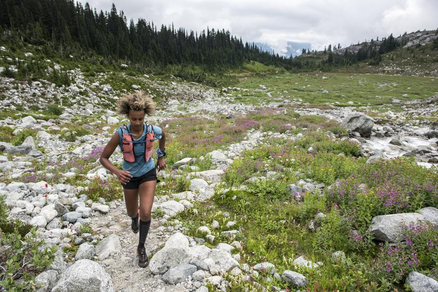 Filsan Abdiaman, a black woman, runs through a rockey valley of pink wildflowers.