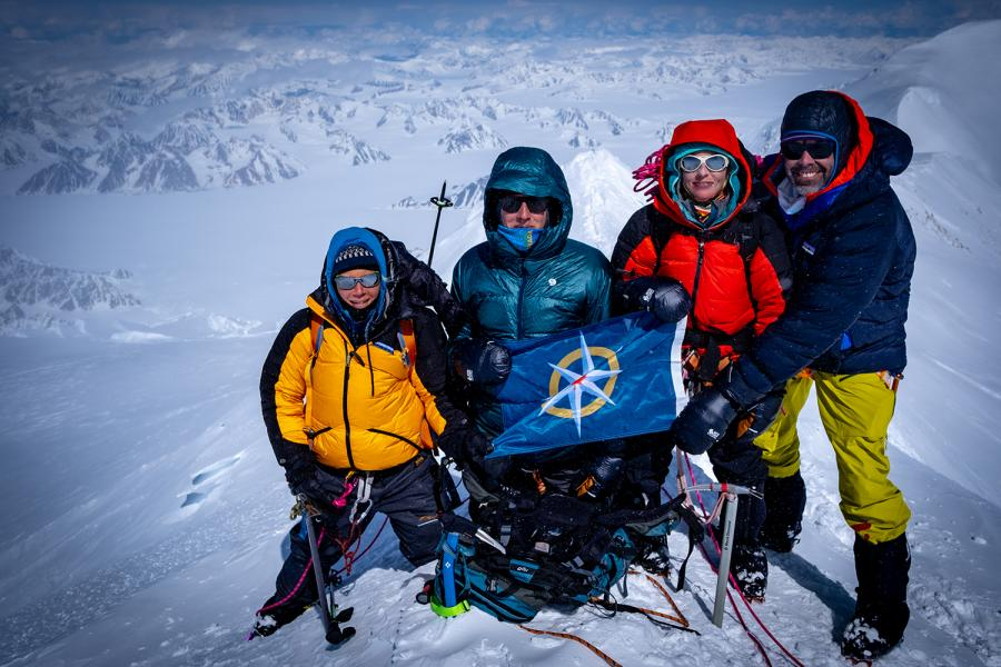 Four mountaineers stand on the summit of mount logan, canada