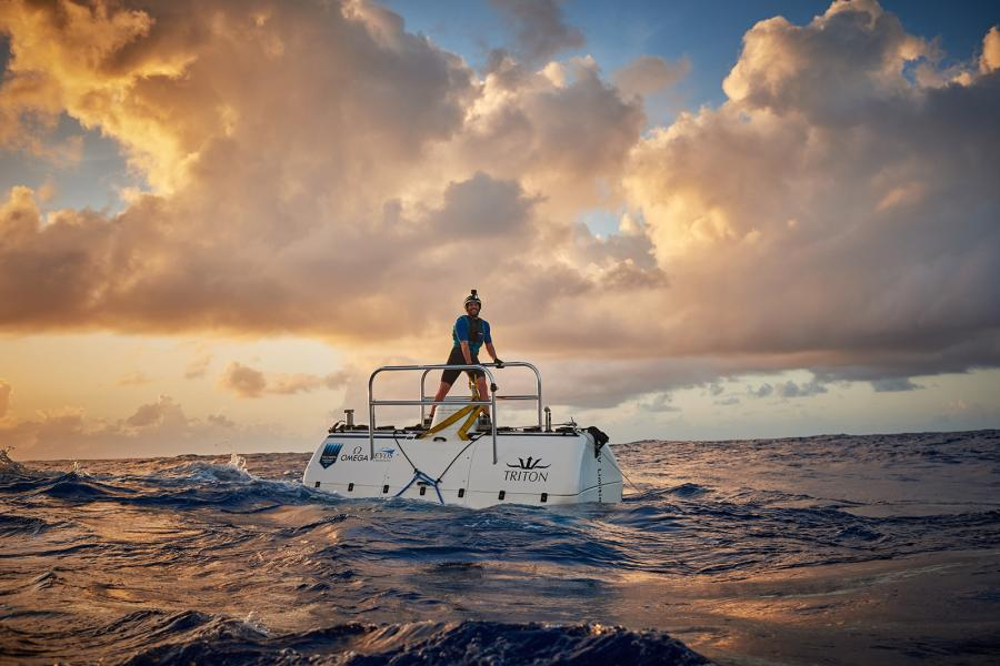 A diver stands on top of a submarine on the sea surface