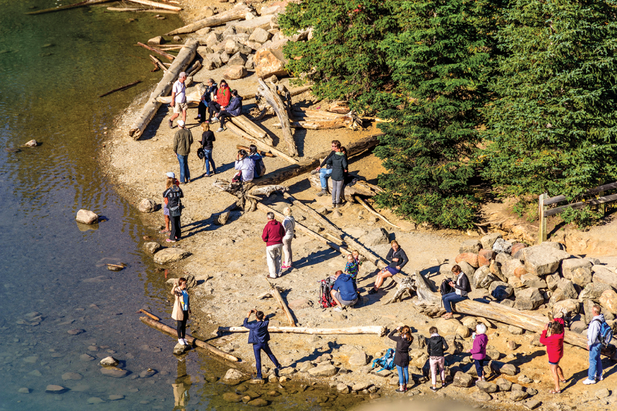 A crowd of tourist swarm on a lakeside beach in Banff National Park