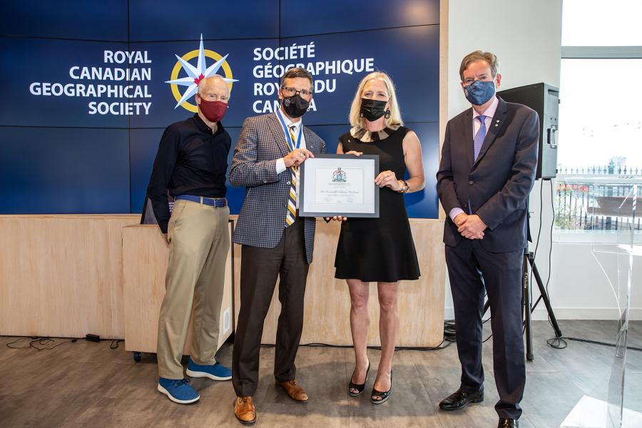 """Four people pose in front of a blue background saying """"Royal Canadian geographical Society."""" They are Dr. Joe MacInnis, Gavin Fitch, Catherine McKenna, and John Geiger"""