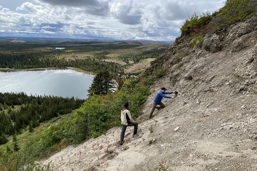 Two men scale a steep cliff above a lake