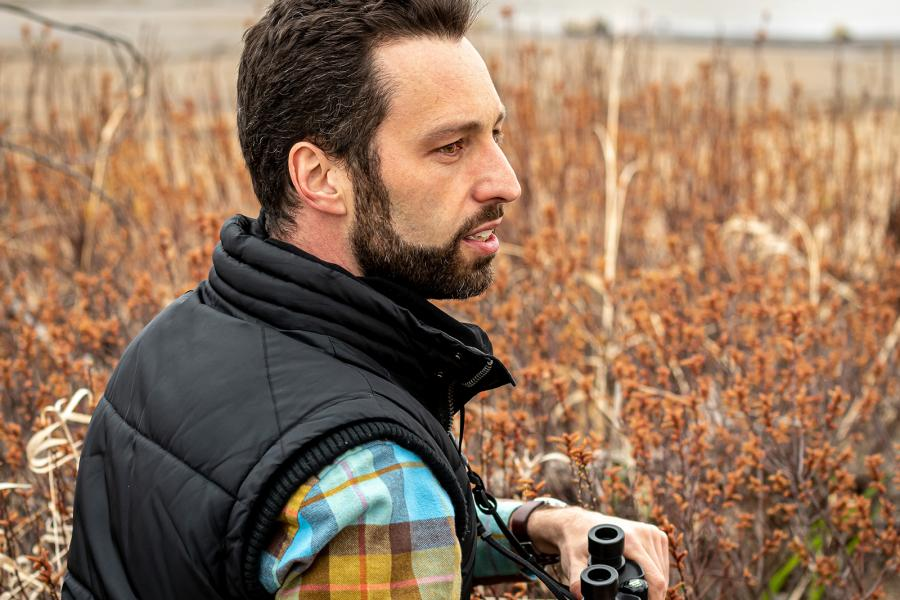 A man holds binoculars while looking out over a brown field