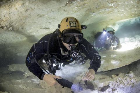 Two divers scuba diving in a cave in the Bahamas
