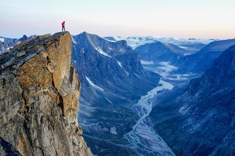 Man on cliff with mountain view.