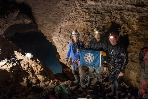 Matt Maddaloni, David Steele, and Adam Walker at the Dieppe Sump with the RCGS flag (Robin Munshaw/Pegleg Films)