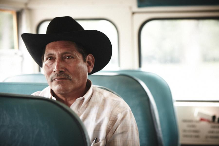 A seasonal migrant workers waits in a school bus, on his way to the Sunday mass. (Photo: Rodolphe Poulin)
