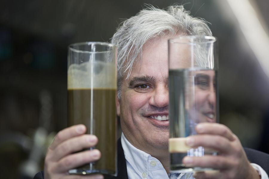 Ross Thurston holds a glass of farm waste water, left, and a glass of clean water that his company's Manure Treatment System can produce from the waste.  (Photo: Peter Power/Canadian Geographic)