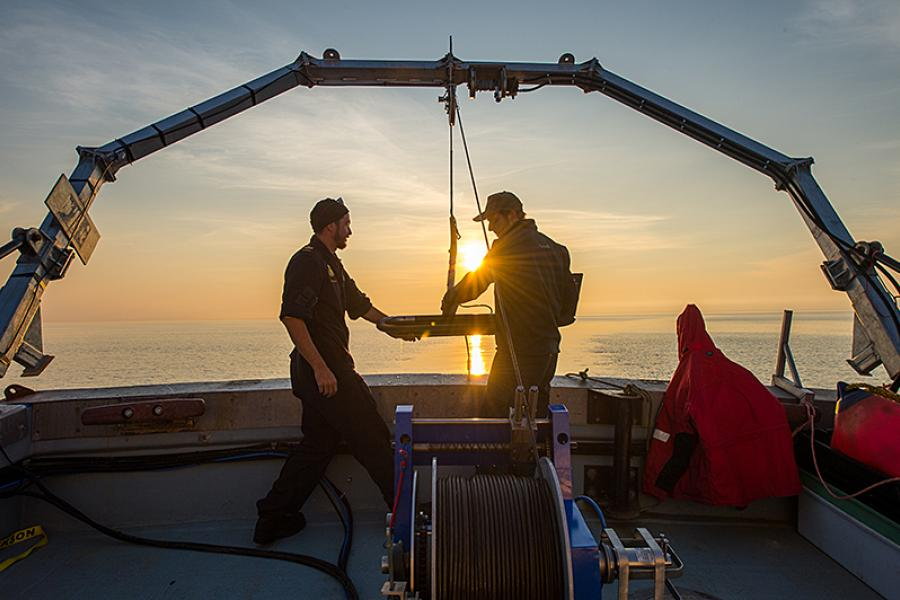 Yves Bernard, a petty officer of the Royal Canadian Navy Fleet Diving Unit, and Ryan Harris, a senior marine archeologist with Parks Canada, raise the side-scan sonar.