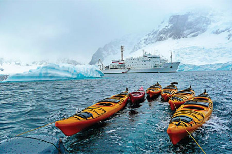 Kayaks point toward the Akademik Sergey Vavilov