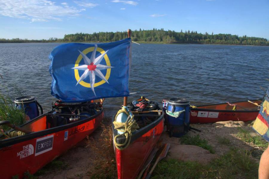 The Royal Canadian Geographical Society flag with the Les chemins de l'or bleu paddling expedition