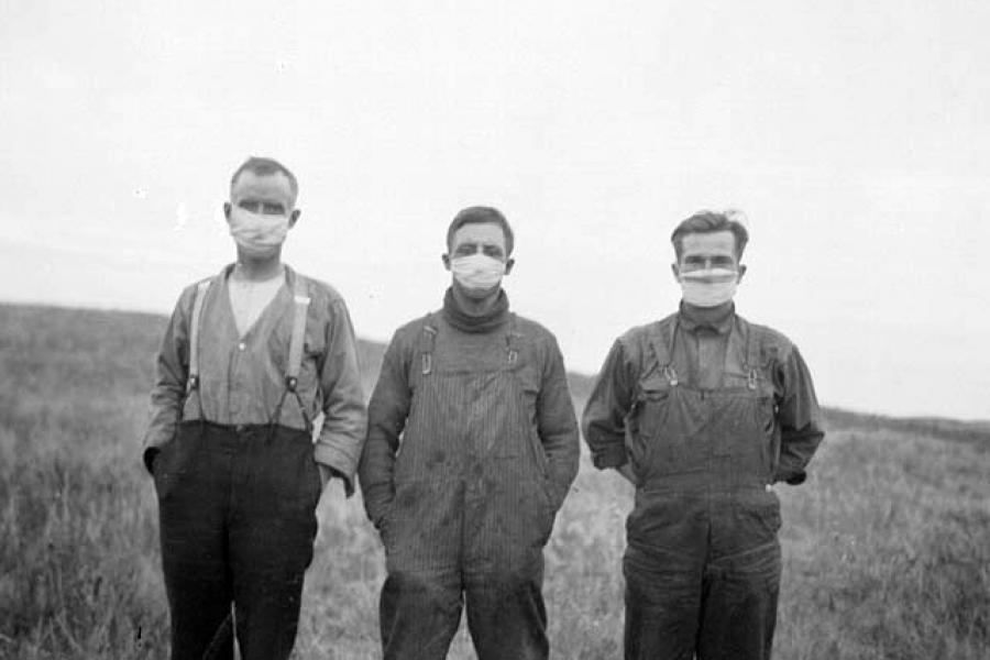 Men in an Albertan field wearing masks during the Spanish Influenza in the fall of 1918.