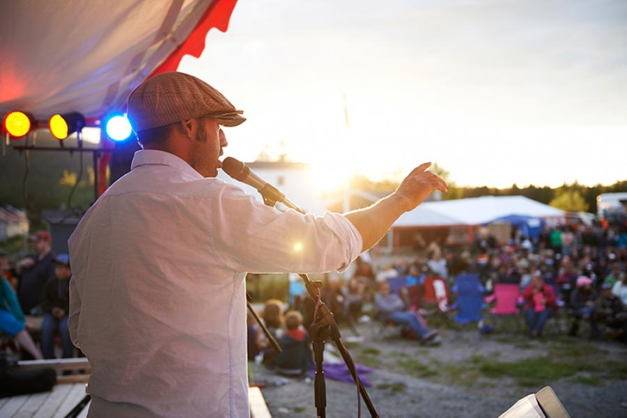 Shaun Majumder addressing the crowd on the main stage as the sun starts to set on the second day of the festival.