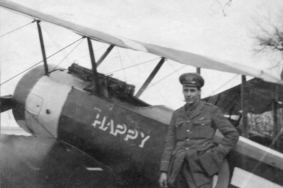 "First World War flying ace Joe Fall stands beside his biplane, ""Happy"""