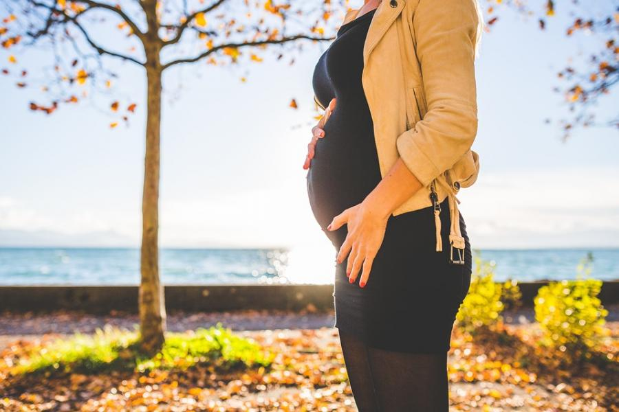Pregnant woman standing in front of water, tree in background, during Autumn.