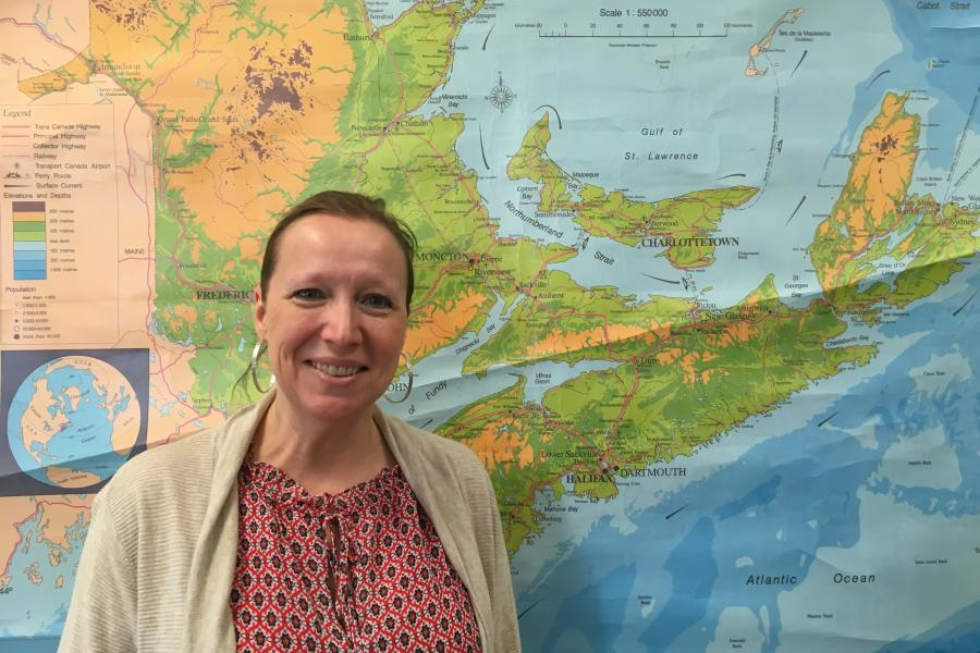 Teacher standing in front of a map of the Maritimes