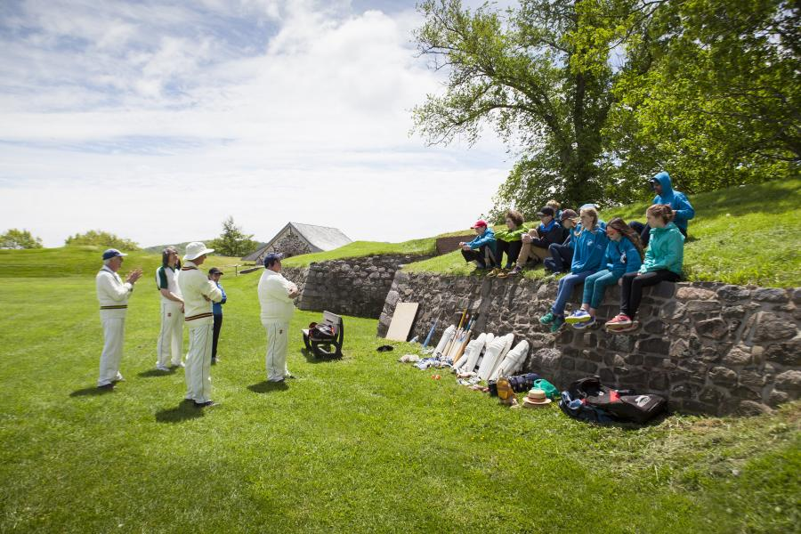 Students learn the rules of cricket at Fort Anne, Nova Scotia