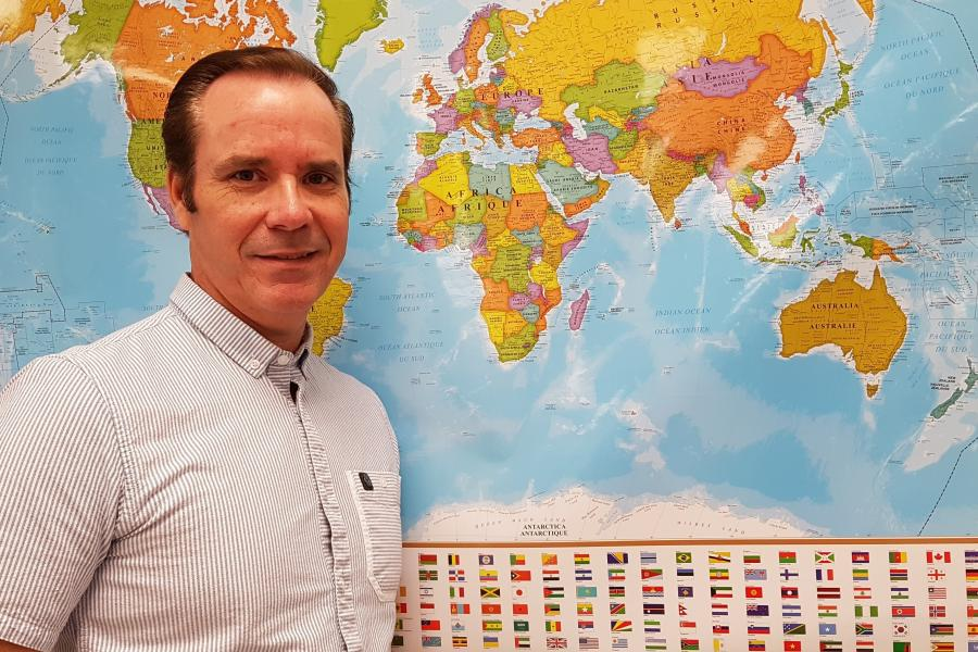 Geography teacher Steve Wohlmuth in front of a world map