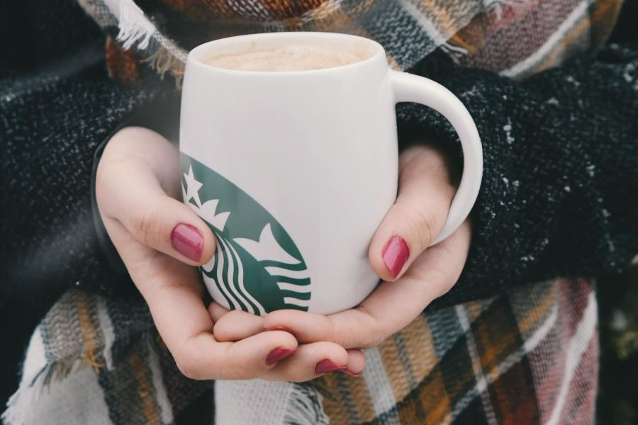 Woman's hands holding Starbucks mug
