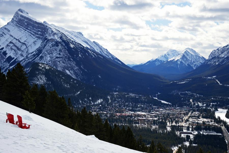 Parks Canada red Muskoka chairs on a snowy slope overlooking the Banff townsite