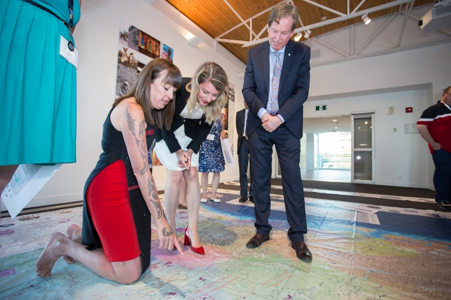 Three people looking down at a giant floor map