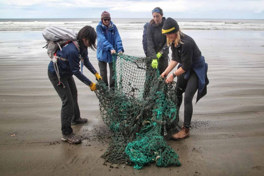 Youth expedition members haul a large fishing net off North Beach during a plastic debris cleanup.