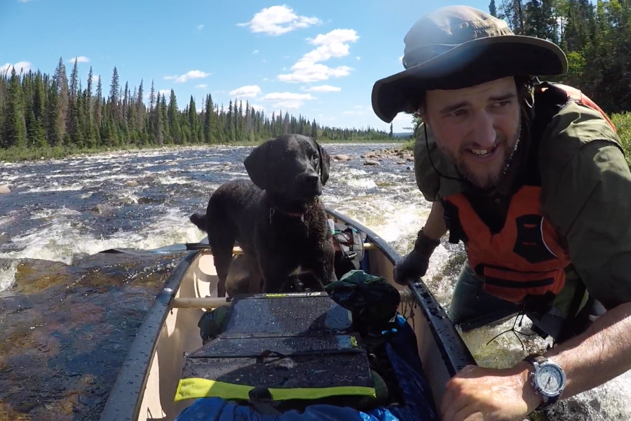 Justin Barbour pulls his canoe upstream with his dog Saku in it