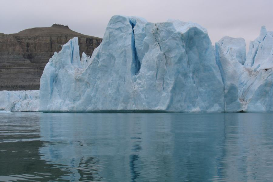 A large blue iceberg floats in the Arctic Ocean