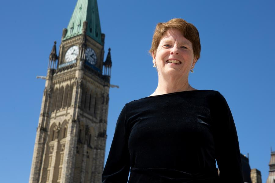 Dr. Andrea McCrady smiles in front of the Peace Tower on Parliament Hill