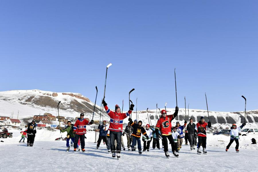 Mark Napier (left) and Lanny McDonald play hockey on the Arctic Ocean with youth from Arctic Bay. (Photo: Michelle Valberg)