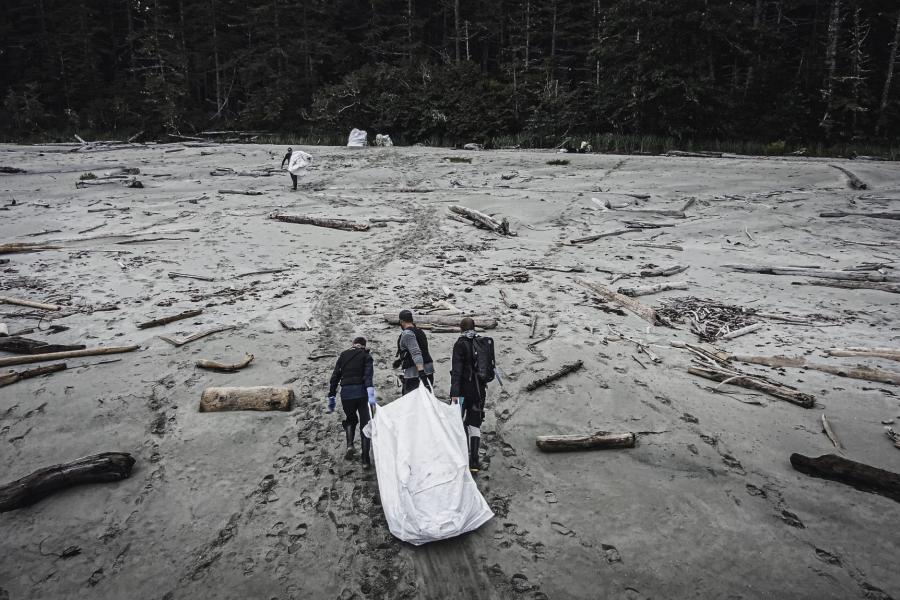people pull debris from ocean