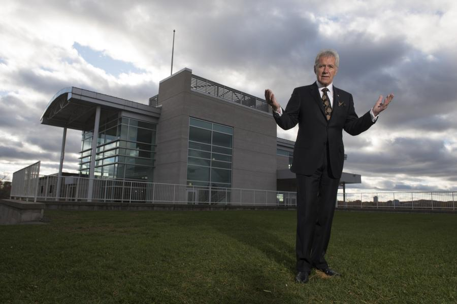 Alex Trebek stands on a lawn with the Royal Canadian Geographic Society headquarters in the background