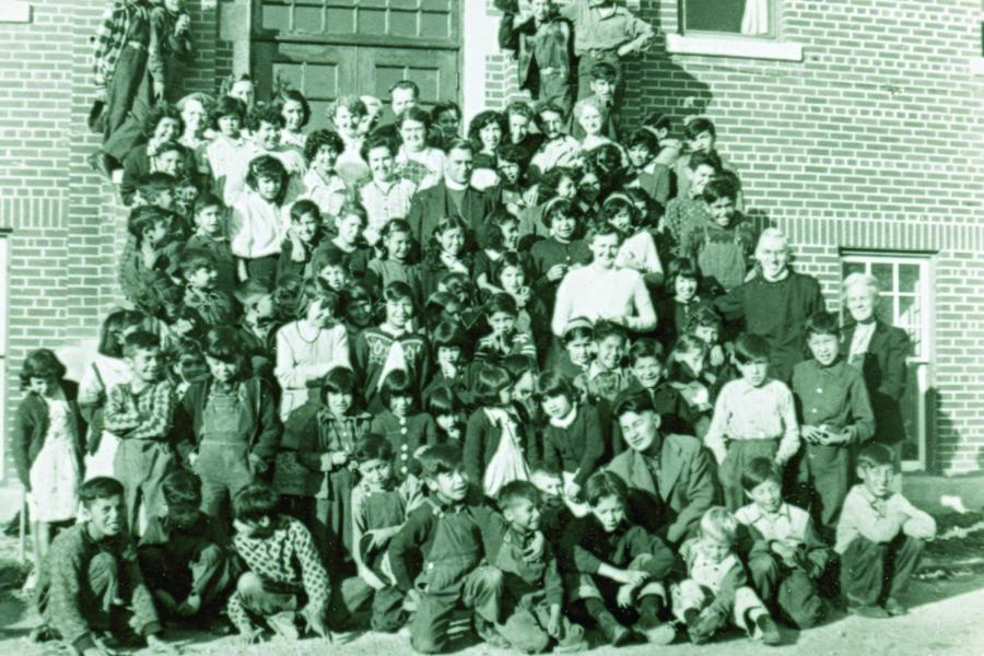 A group of students and staff pose on the steps of Gordon's Residential School in a faded photo.
