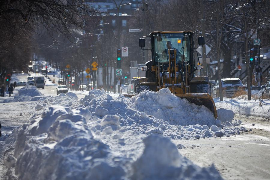 A snowplow pushes snow down the street.