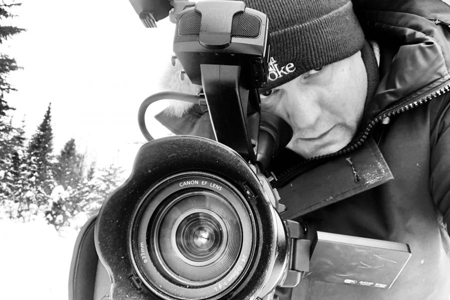 A black-and-white photo of a film maker looks through the lens of his camera