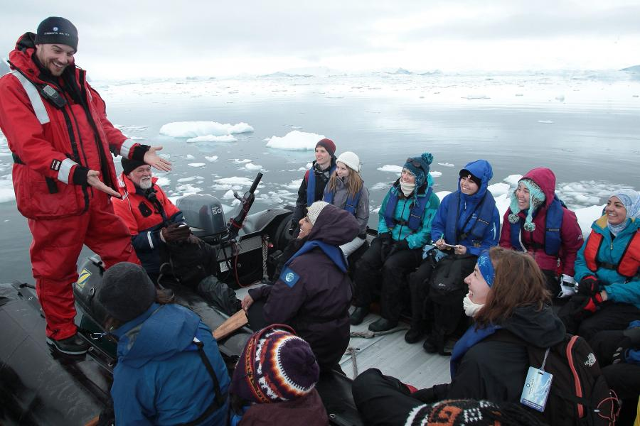 A Student on Ice teacher talks to students in a small boat surrounded by ice