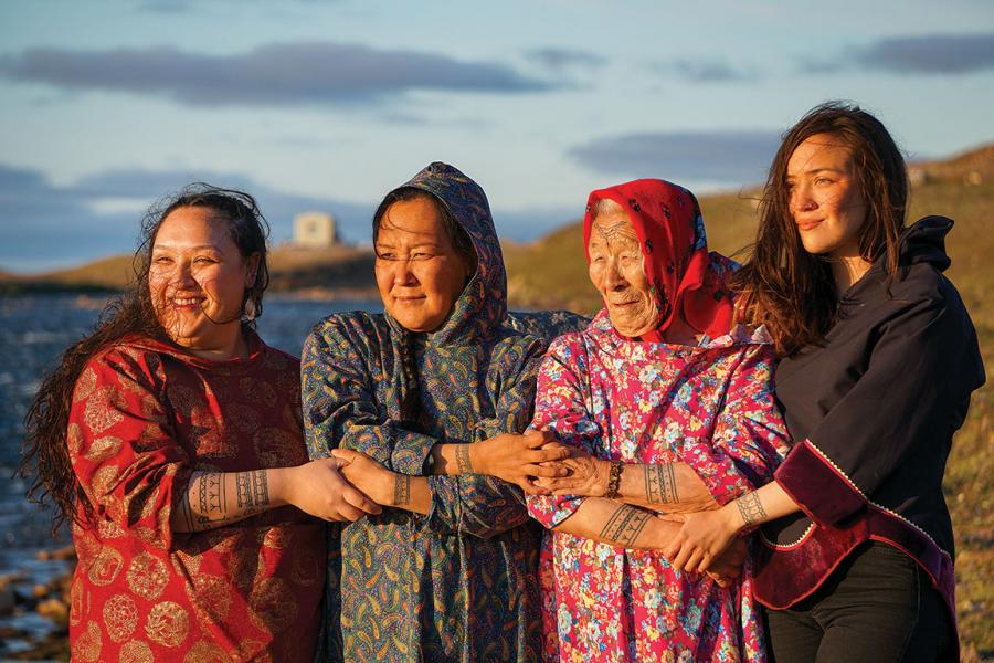 four inuit women stand on the shore showcasing their tattoos