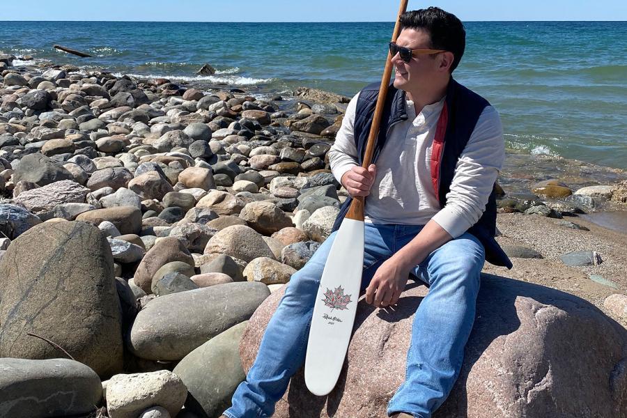 Patrick hunter sits with artisan canoe paddle
