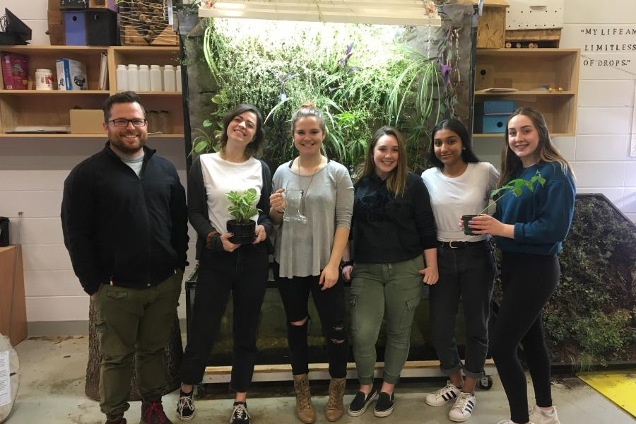 Teacher stands with his students in front of a green wall they've created for the Energy and Environmental Innovation program at the Career and Technology Centre in Calgary