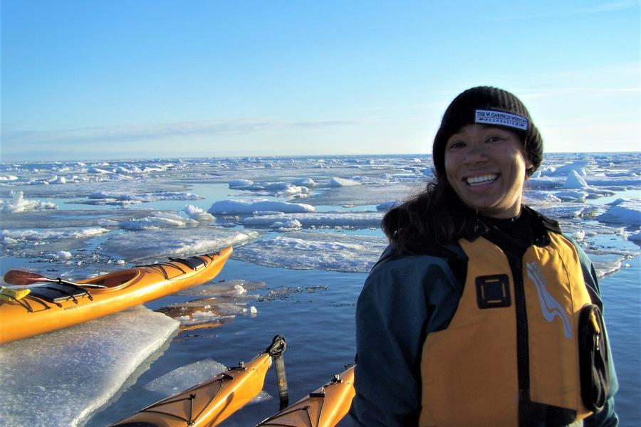 Emily Choy stands in front of artic ice and ocean wearing a yellow lifejacket, alongside three yellow kayaks