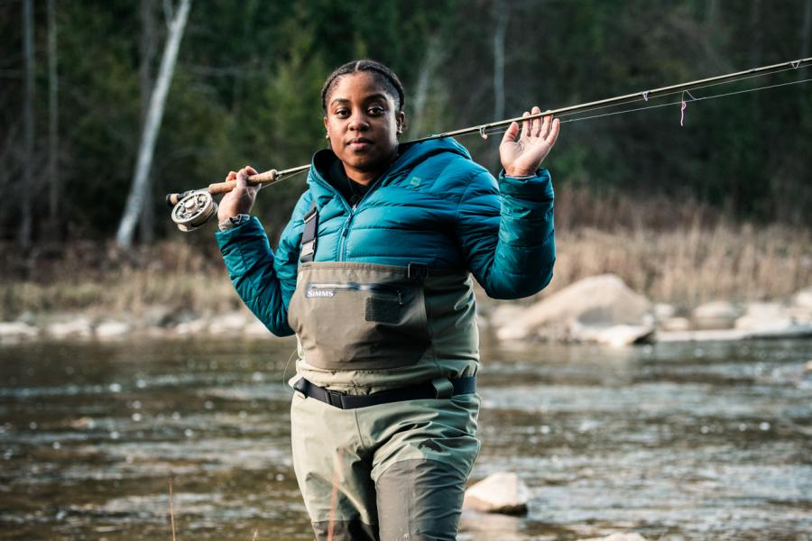 A woman dressed in fishing gear and a blue-green coat holds a fishing rod over her shoulders in a river