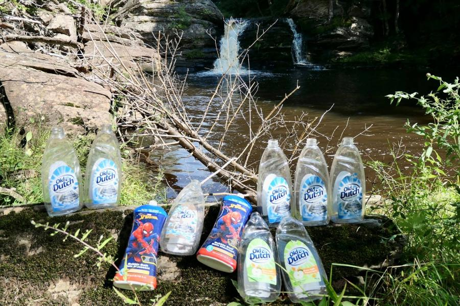 Empty dish soap bottles arrayed in front of a pond in Nova Scotia