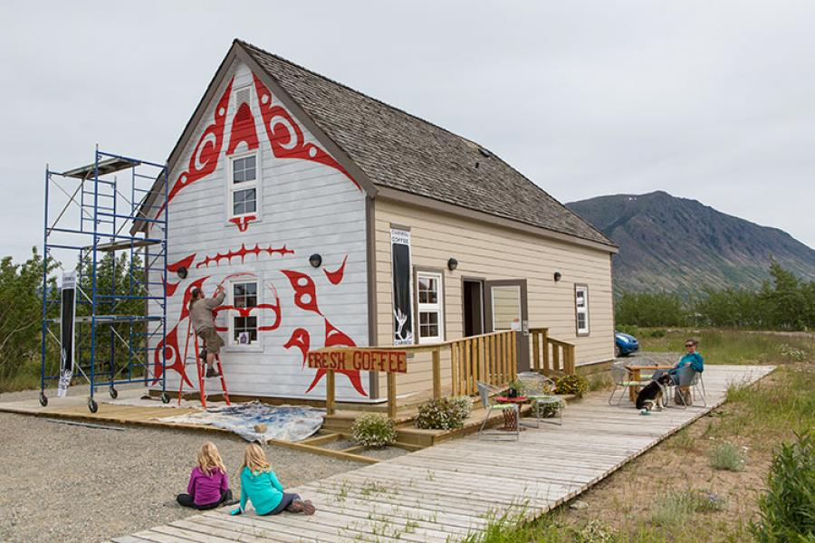 A muralist paints a Keith Wolfe-Smarch design on a replica of Skookum Jim's house in Carcross, Yukon