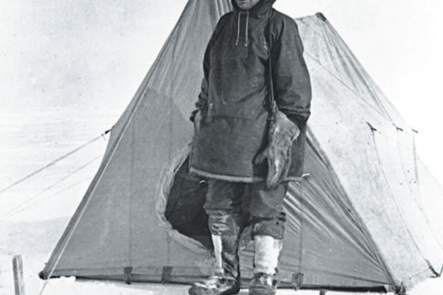 Anderson stands in front of a tent at Collinson Point, Alaska, in 1914.