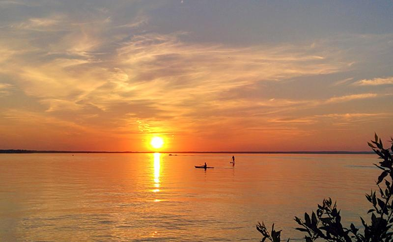 A paddleboarder and a kayaker on Clear Lake in Riding Mountain National Park in Manitoba at sunset. (Photo: Harry Wilson/Canadian Geographic)