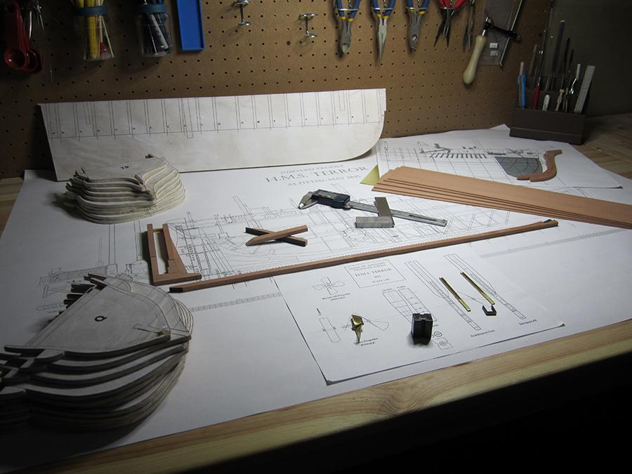 The work table with finished parts, plans, tools, and materials for the construction of a model of the iron storage tank located in Terror's stern.