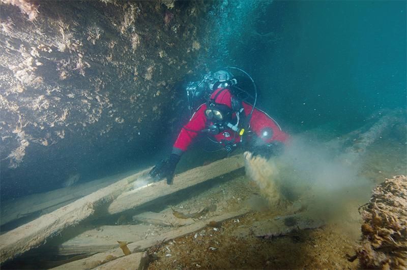 A Parks Canada archeologist inspects debris next to Erebus's hull