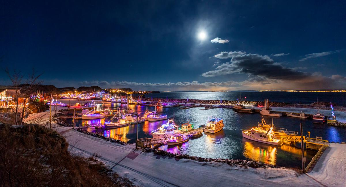 A full moon shines above boats decked out with holiday lights in Port de Grave, Nfld.