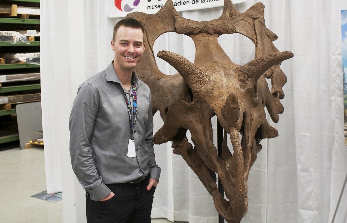"Dr. Jordan Mallon of the Canadian Museum of Nature poses with the skull of ""Judith,"" a new species of dinosaur"